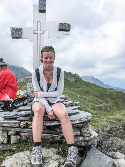 Frau sitzt vor Gipfelkreuz aus hellem Metall mit Steinen an den Ecken - dahinter Berggipfel