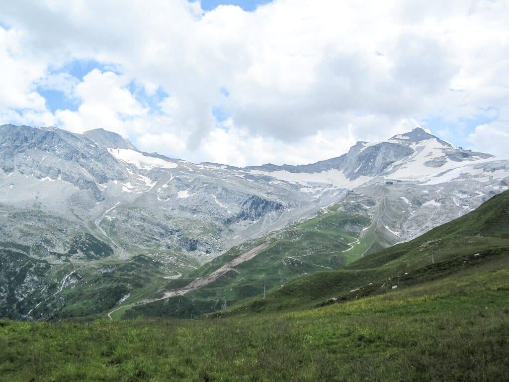 grüne Wiese - dahinter schneebedeckte Berggipfel