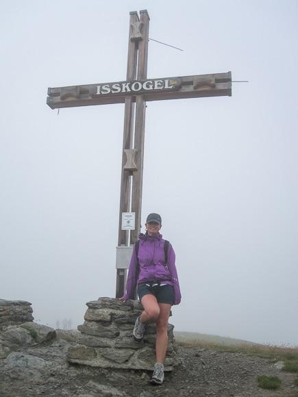 Frau steht im Nebel am Gipfelkreuz