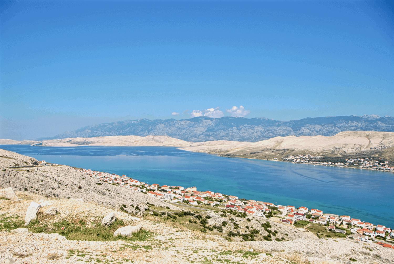 Ausblick über sanfte Hügel und ein Dorf mit dem Meer