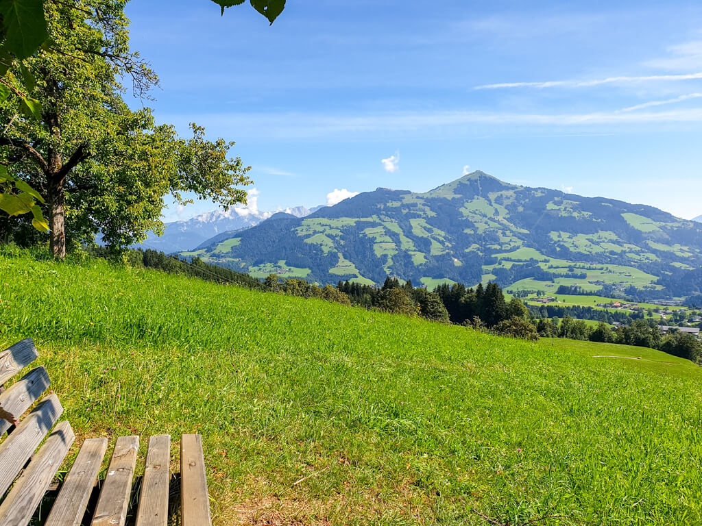 Bank mit Aussicht über Wiesen und auf die Berge in Hopfgarten