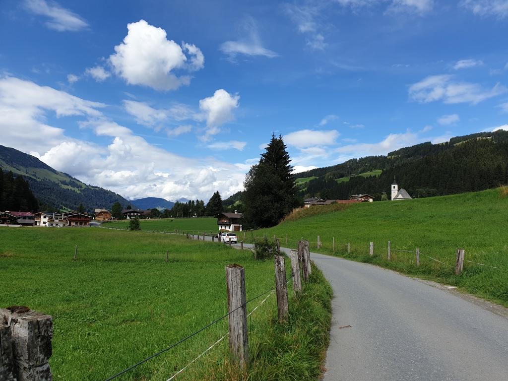 Straße führt inmitten von Wiesen nach Aschau