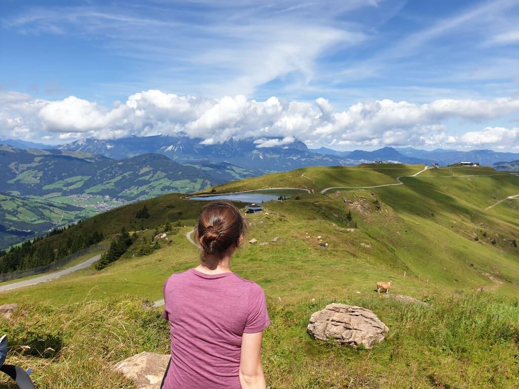 Frau sitzt in den Bergen und blickt in die Ferne
