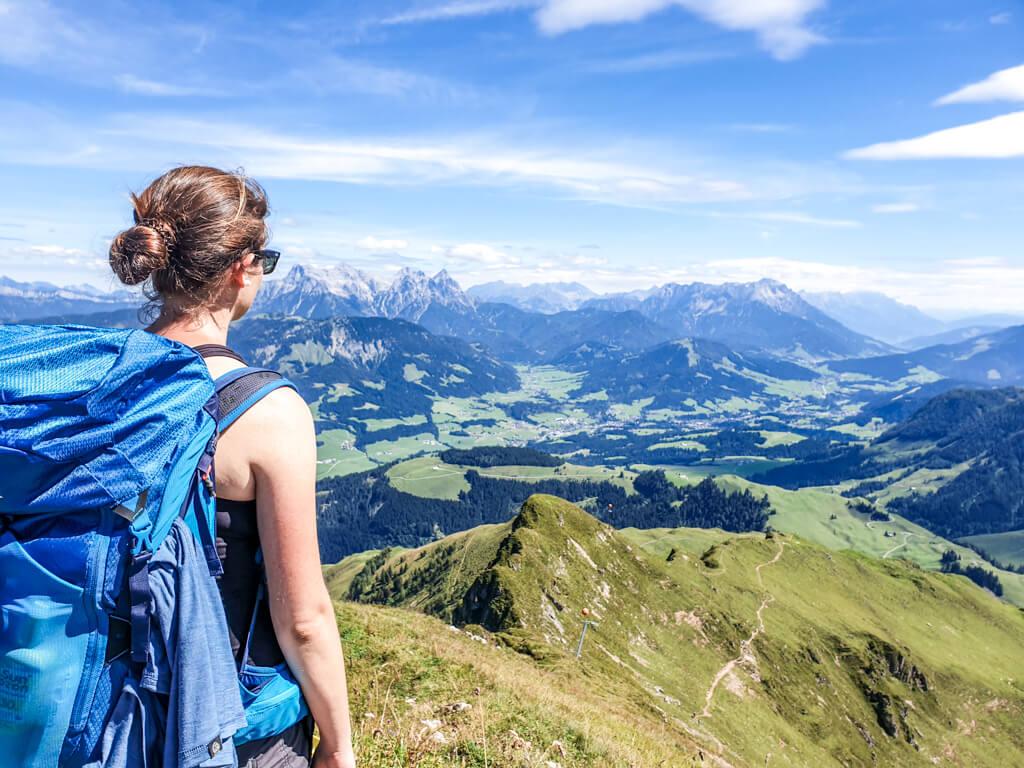 Frau mit Wanderrucksack schaut über die Berge in die Ferne