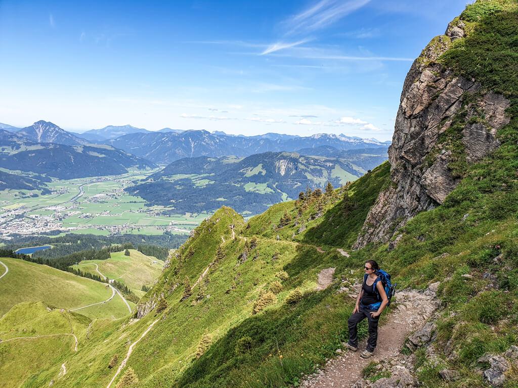 Frau steht auf einem schmalen Wanderweg beim Abstieg vom Kitzbüheler Horn mit Blick über grüne Berge
