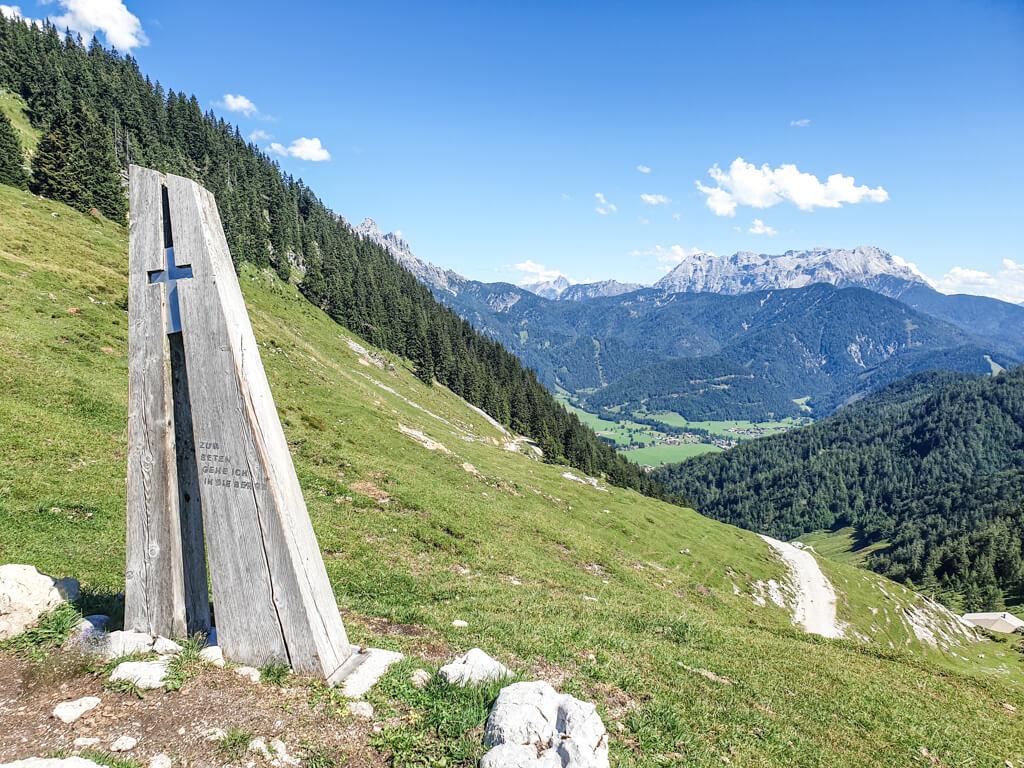 Holzkreuz in St. Ulrich am Pillersee mit Blick auf grüne Berge im Hintergrund