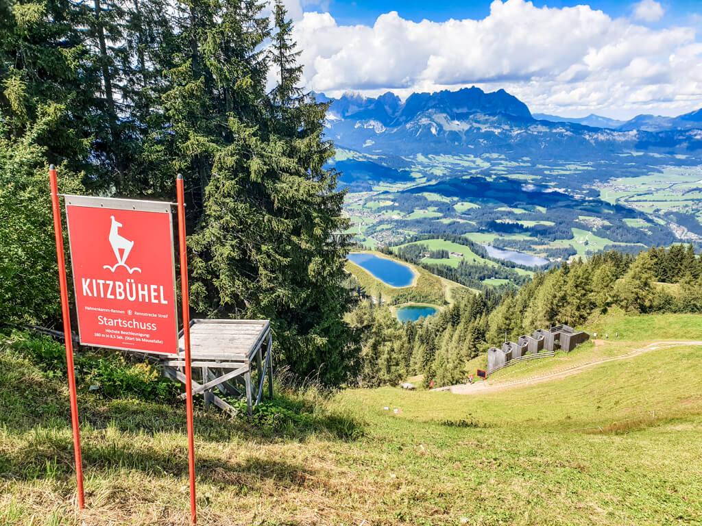 Blick auf Kitzbühel mit zwei Speicherseen; im Vordergrund eine Tafel der Hahnenkamm-Rennstrecke im Sommer