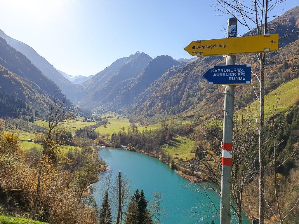 Wegweiser für einen Wanderweg auf einem Hügel, dahinter ein Bergsee