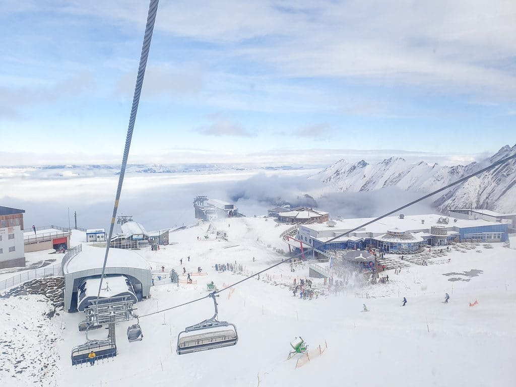 Sessellift über schneebedeckten Bergen mit blauem Himmel