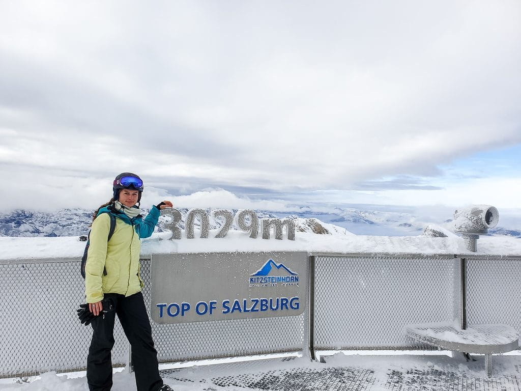 Frau steht auf einer Aussichtsplattform mit Blick auf Berggipfel