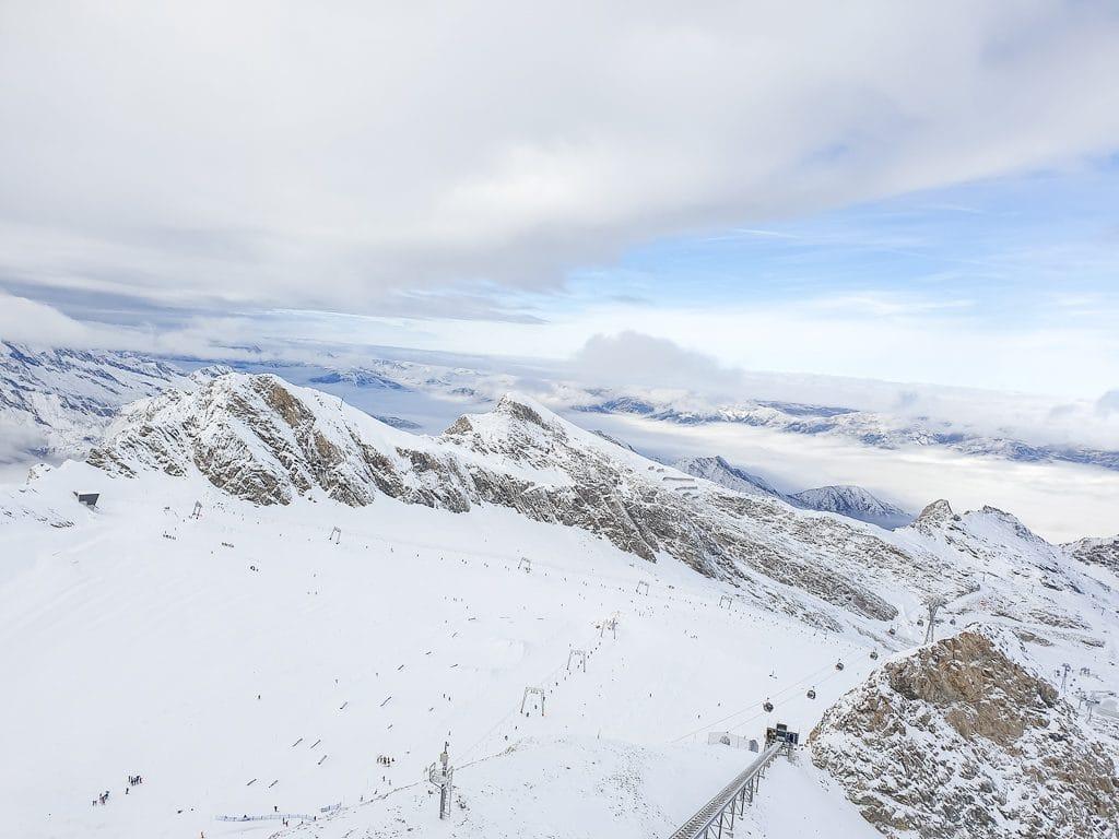 Verschneite Berggipfel und ein Lift über einer Piste