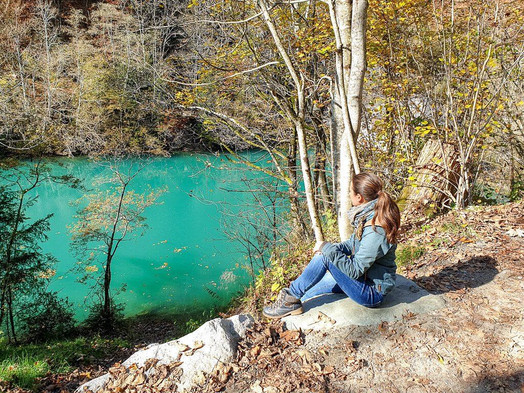 Frau sitzt auf einem Stein und blickt auf einen See