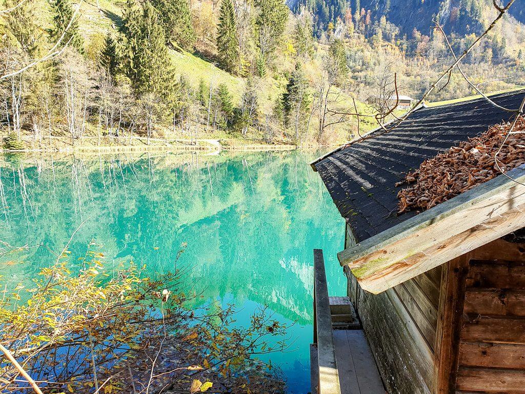 Berghütte mit Blick auf einen türkis-grünen See