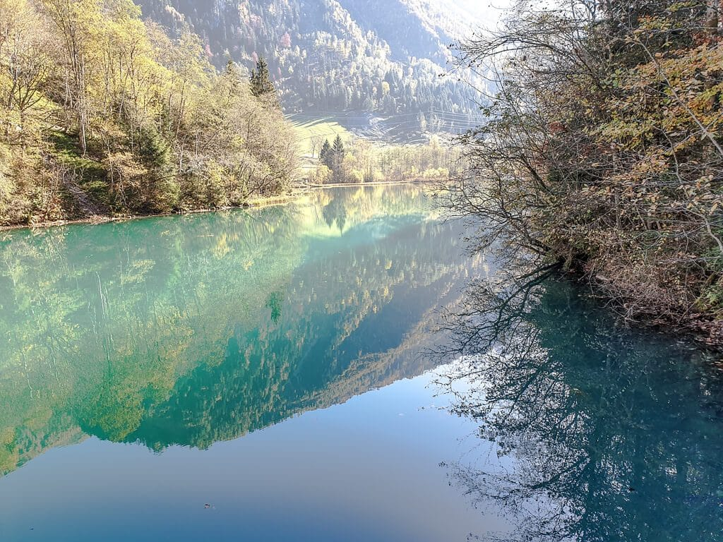 Kaprun - Bergsee mit Spiegelungen von herbstlich gefärbten Bäumen auf dem Wasser