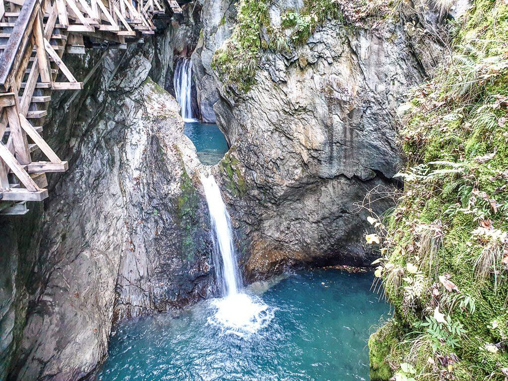 leuchtend blaues Wasser mit einem kleinen Wasserfall in einer Klamm
