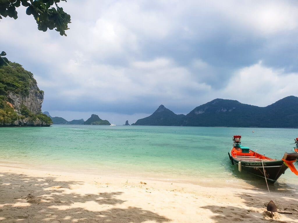 Sandstrand mit Longtailboot und Blick auf das Meer mit kleinen Inseln