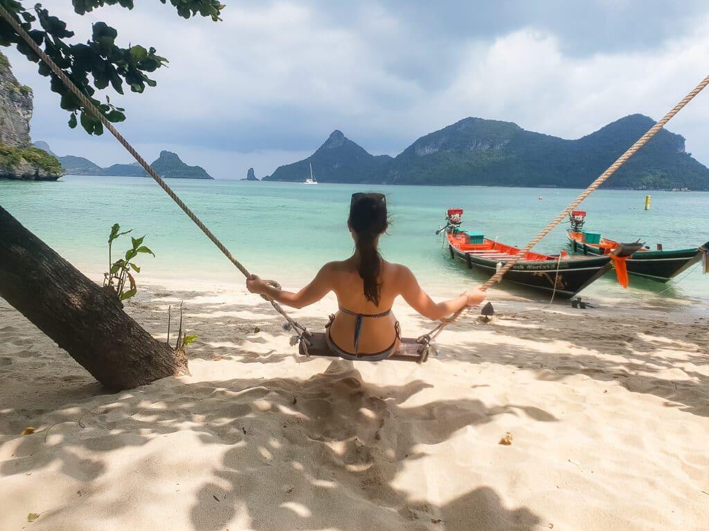 Frau schaukelt auf einer Schaukel am Strand mit Blick auf das Meer mit Longtailbooten