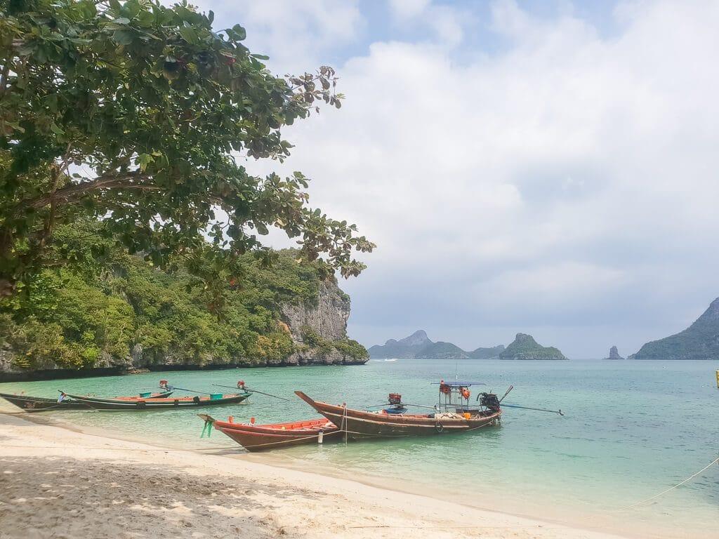 Longtailboote im flachen Wasser, daneben ein Sandstrand und im Hintergrund kleine Insel mit Felsen