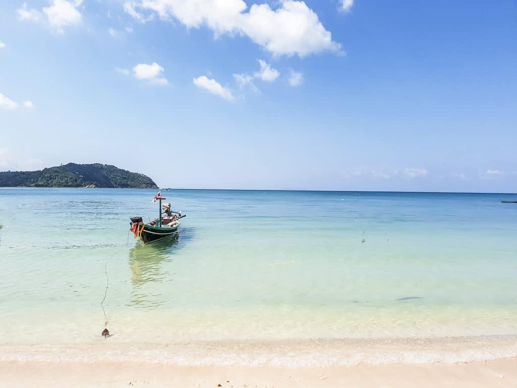Boot liegt im türkisen Wasser direkt am Sandstrand