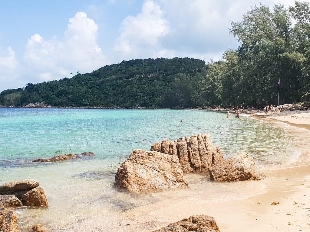 große Steine am Sandstrand, daneben das Meer und ein grün bewachsener Hügel