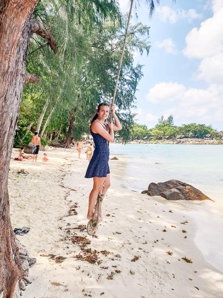 Frau schwingt an einem Seil am Strand