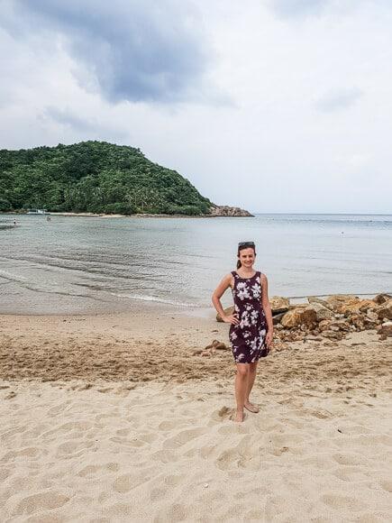 Frau steht am Strand - dahinter das Meer und eine kleine Insel