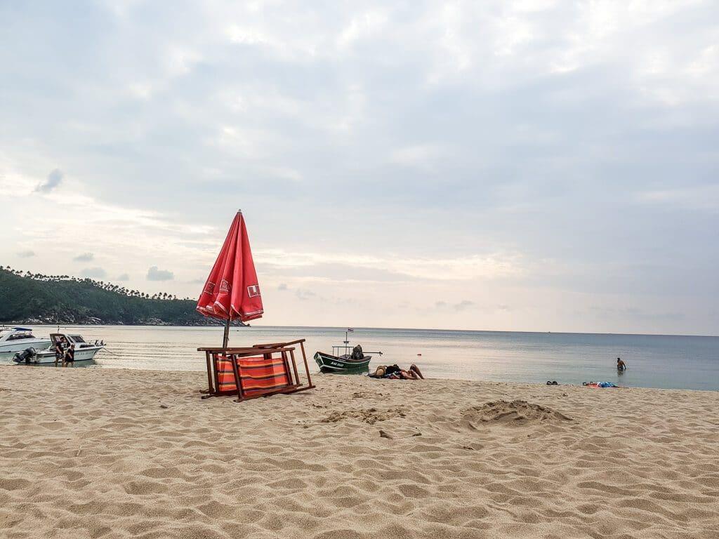 Strand mit Blick auf das Meer - in der Mitte des Bildes ein Stuhl mit Sonnenschirm
