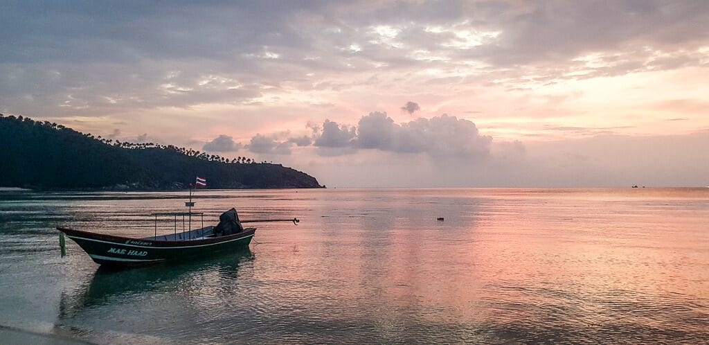 Sonnenntergang über dem Meer - links im Bild ein Boot