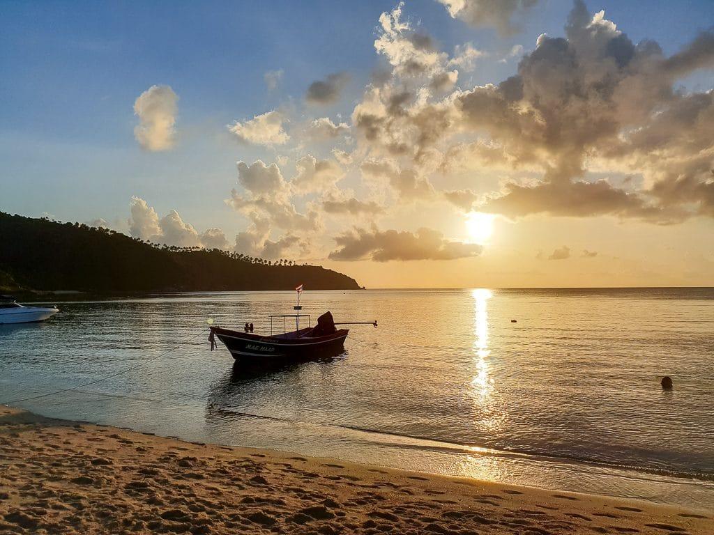 Sonnenuntergang über dem Meer, auf dem Meer ein Boot und im Vordergrund ein Strand