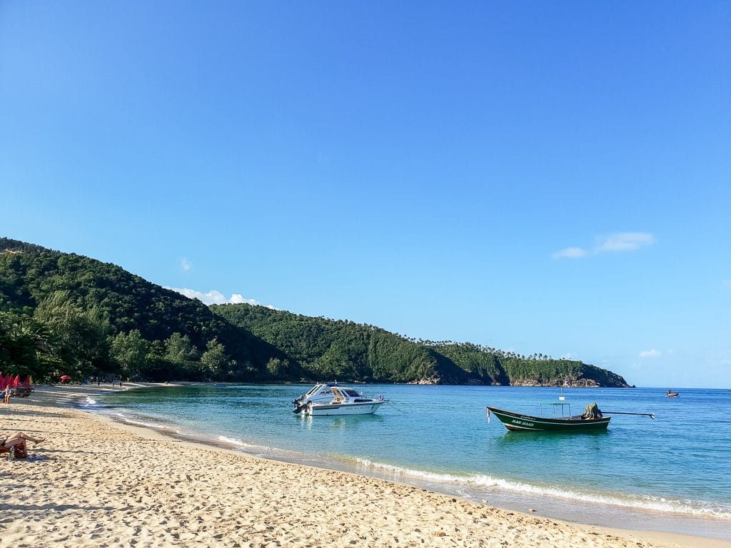 Bucht mit hellem Strand, grünen Hügeln und zwei Booten im Wasser