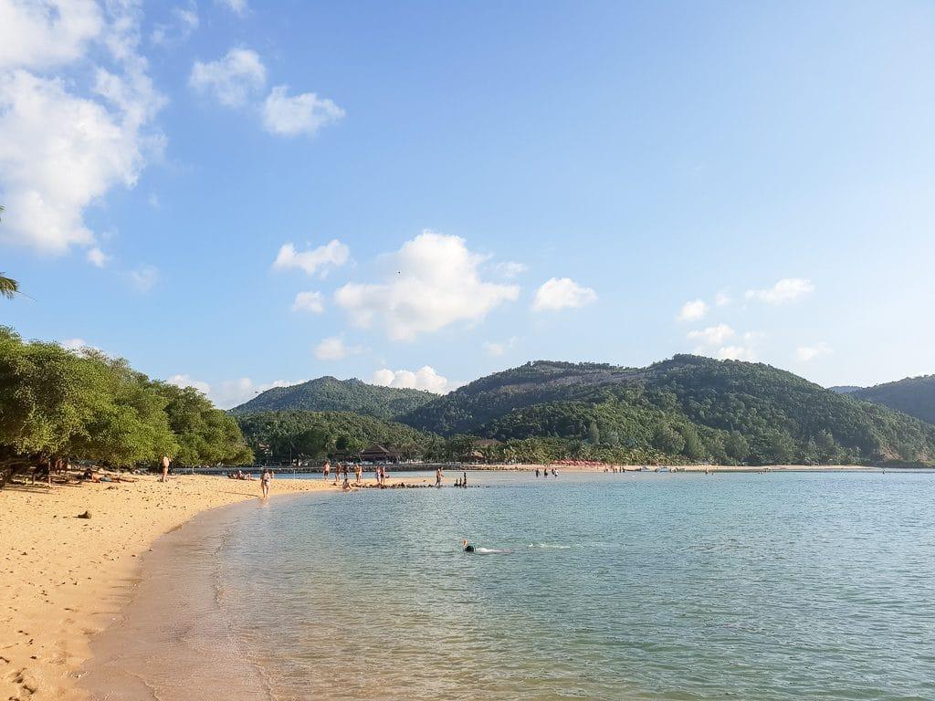 Bucht mit Sandstrand und Meer - an Land grün bewachsene Hügel