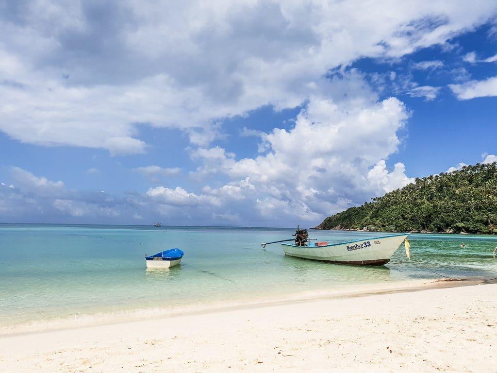 Strand mit Booten im Meer und kleinem grünen Hügel rechts