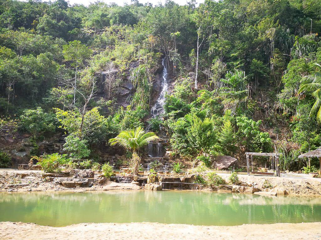 Wasserfall im Wald - unten ein kleiner See umgeben von Sand