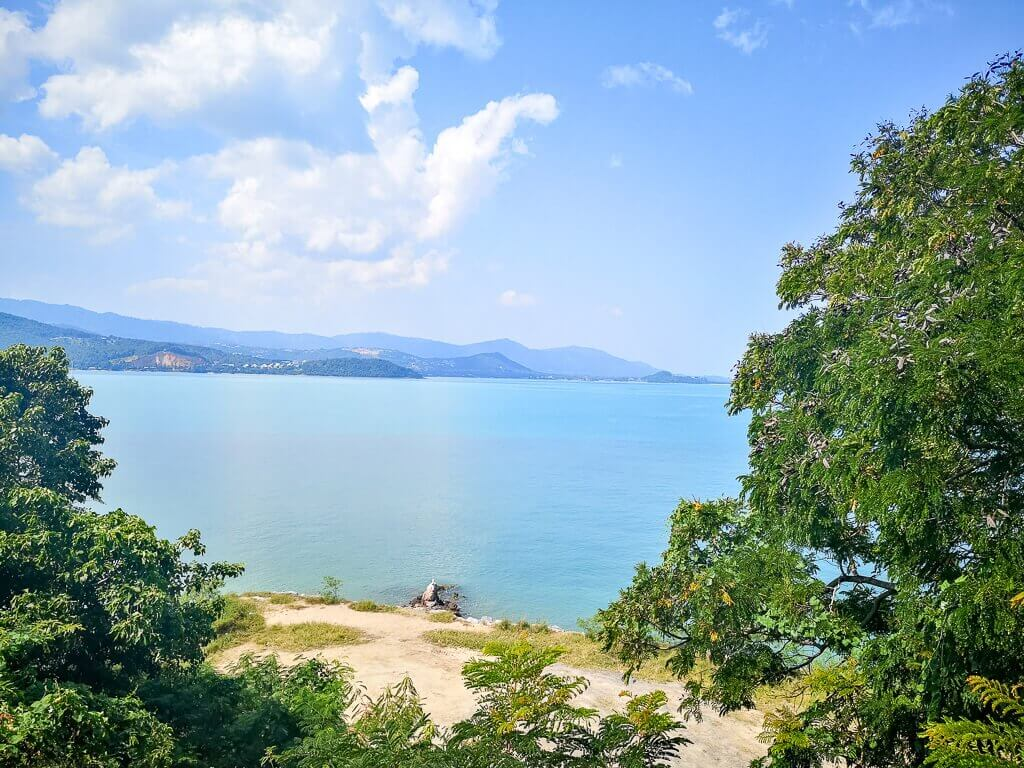 Strand auf Ko Samui - Bäume an beiden Seiten mit Blick auf das Meer und Hügel im Hintergrund