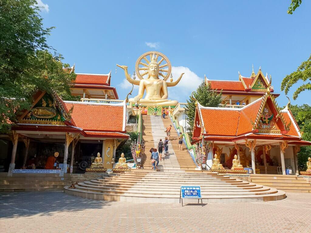Big Buddha Statue Ko Samui; farbige Treppenstufen führen nach oben zur goldenen Statue; rechts und links befinden sich Tempelgebäude
