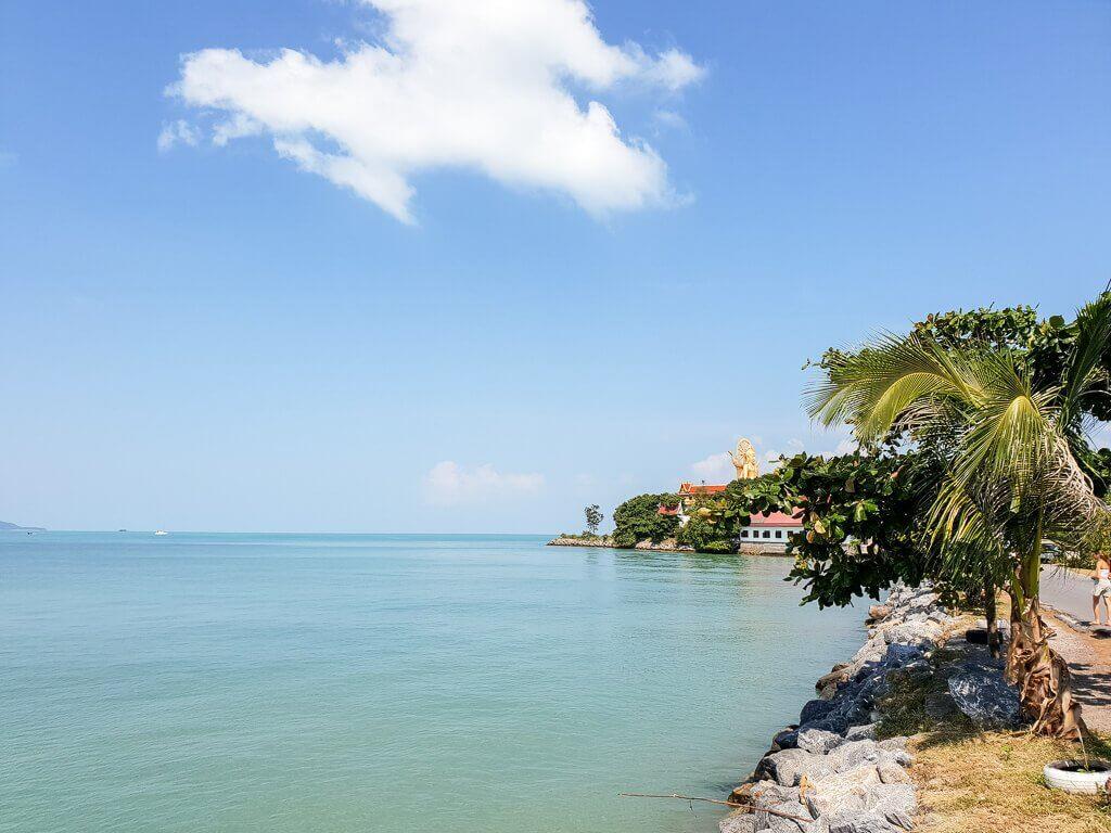 Ko Samui - Blick auf den Big Buddha aus der Ferne; Meer und Strand mit Palmen im Vordergrund