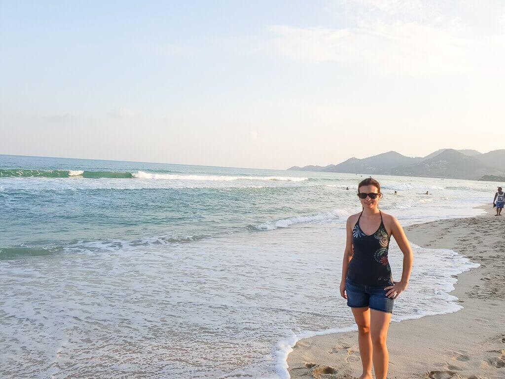 Ko Samui - Chaweng Beach - Frau steht am Strand in den Wellen des Meeres