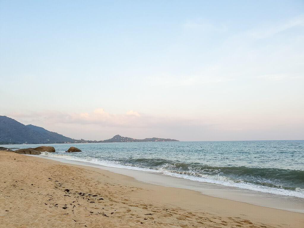 Strand mit Bergen am linken Rand; Wellen treffen auf den Strand