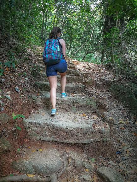 Frau klettert über hohe Steinstufen einen Berg im Wald hinauf