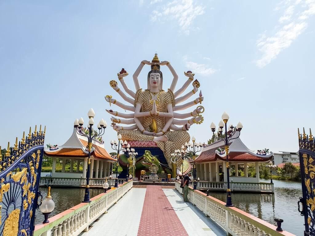 Wat Plai Laem Ko Samui; ein Weg führt über einen See zur 18-armigen Statue