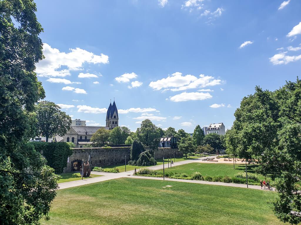 Blick über eine große Parkanlage mit Wiesen - dahinter eine Kirche mit zwei Türmen