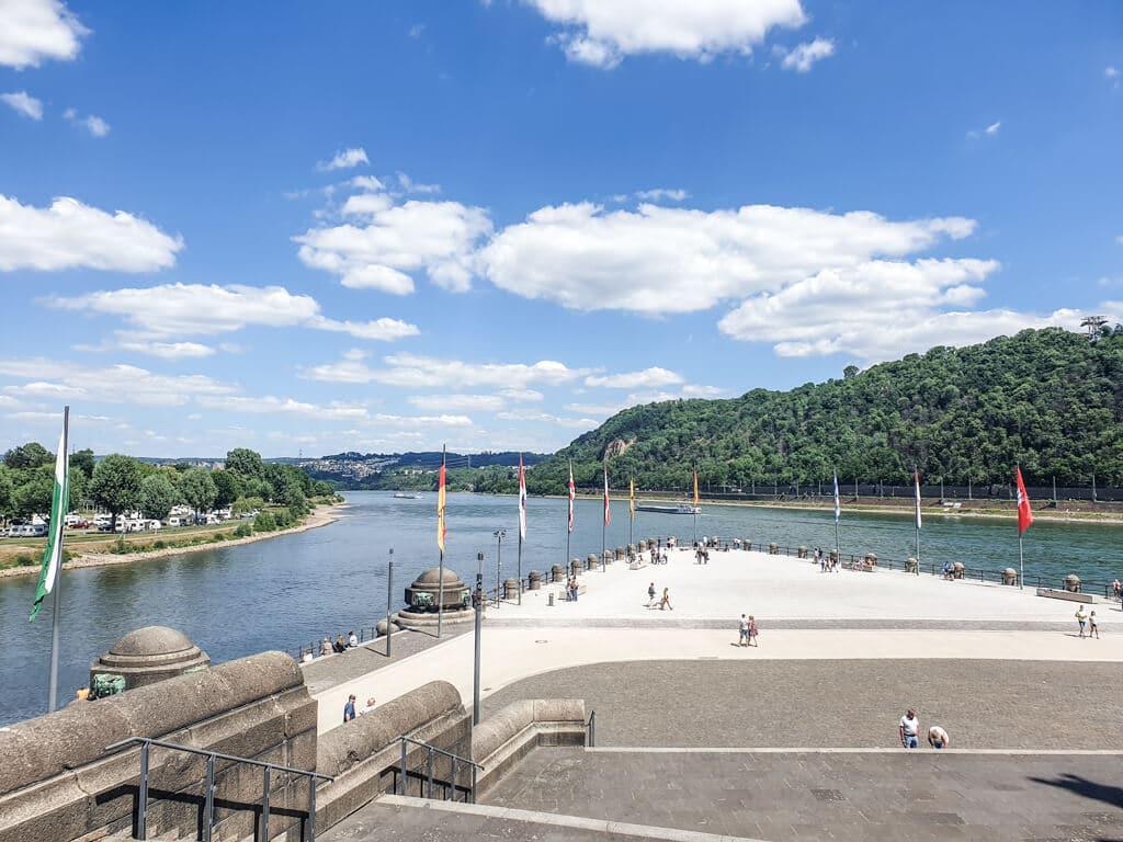 Blick über einen großen Platz mit Länderflaggen auf den Zusammenfluss von Rhein und Mosel am Deutschen Eck