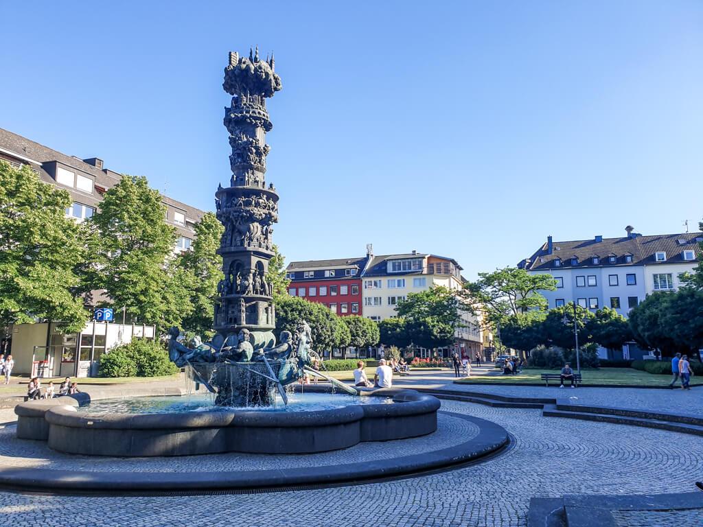 Brunnen mit großer Säule mit verschiedenen Figuren auf einem großen Platz