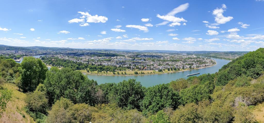 """Aussicht auf eine weite Kurve am Rhein vom """"Rhein-Mosel-Blick""""- auf der anderen Rhein-Seite ist die Stadt Koblenz zu sehen"""