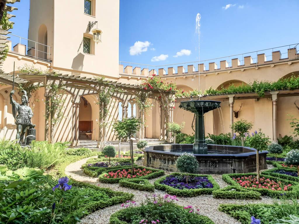 Garten mit mehreren Beeten und einem Brunnen in der Mitte, umgeben von Laubengängen im Schloss Stolzenfels