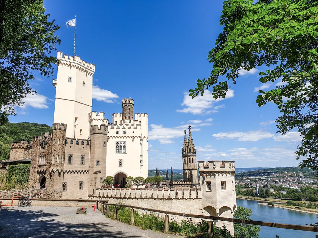 Blick auf Schloss Stolzenfels aus hellem Sandstein und mit vielen kleinen Türmchen und Zinnen. Rechts unter dem Schloss liegt der Rhein