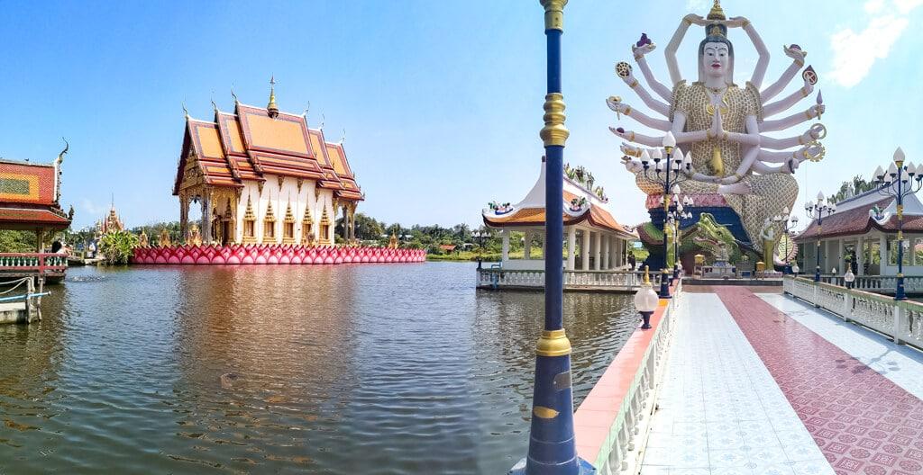 18-armige Statue in einem Tempel auf Thailand - rundherum ein See und weitere bunte Tempel
