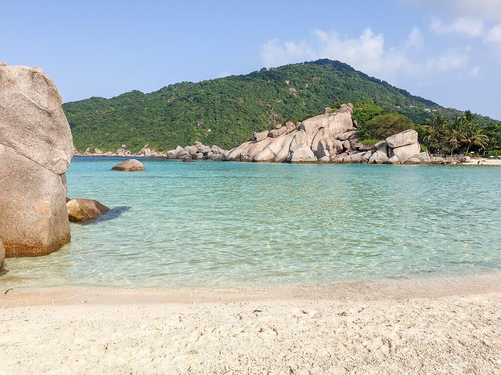 Strand mit großen Felsen, dahinter türkises Meer und eine weitere Insel