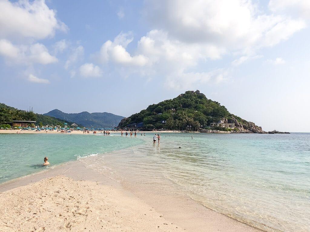 Sandbank im türkisen Meer, dahinter eine Insel mit grünen Hügeln