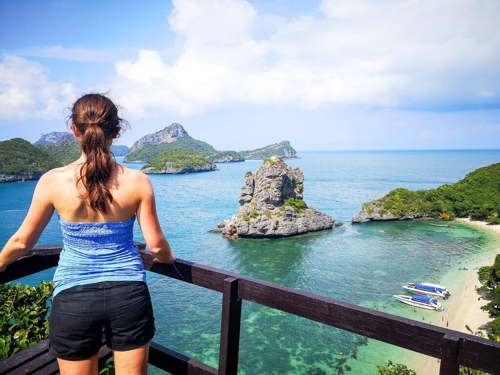 Frau steht mit Blick auf das Meer - Blick auf einen Sandstrand und das Meer mit kleinen Inseln